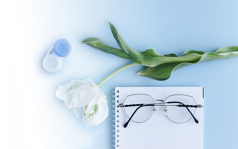 Очки и цветы на белом фоне